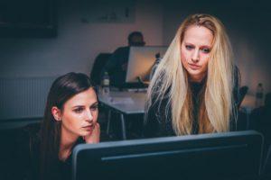 Two businesswomen at office desk thinking